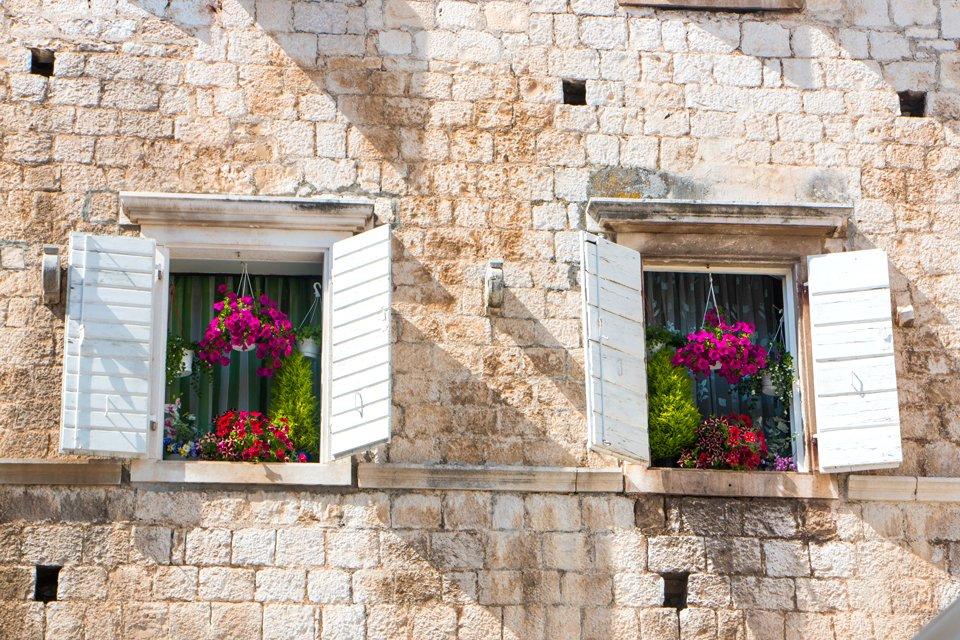 Met bloemen versierde ramen in Trogir, Kroatië